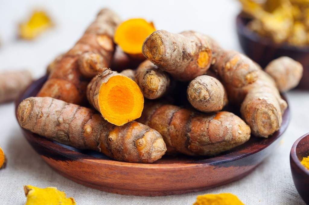 fresh-and-dried-turmeric-roots-in-a-wooden-bowl-picture-id690557976