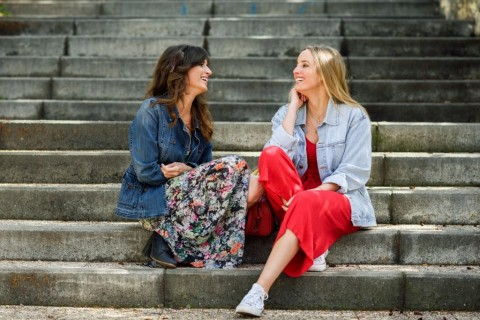 two-young-women-talking-and-laughing-on-urban-steps-picture-id937697796