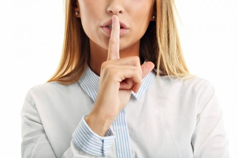 adult-woman-holding-a-finger-on-her-lips-over-white-background-picture-id663991088