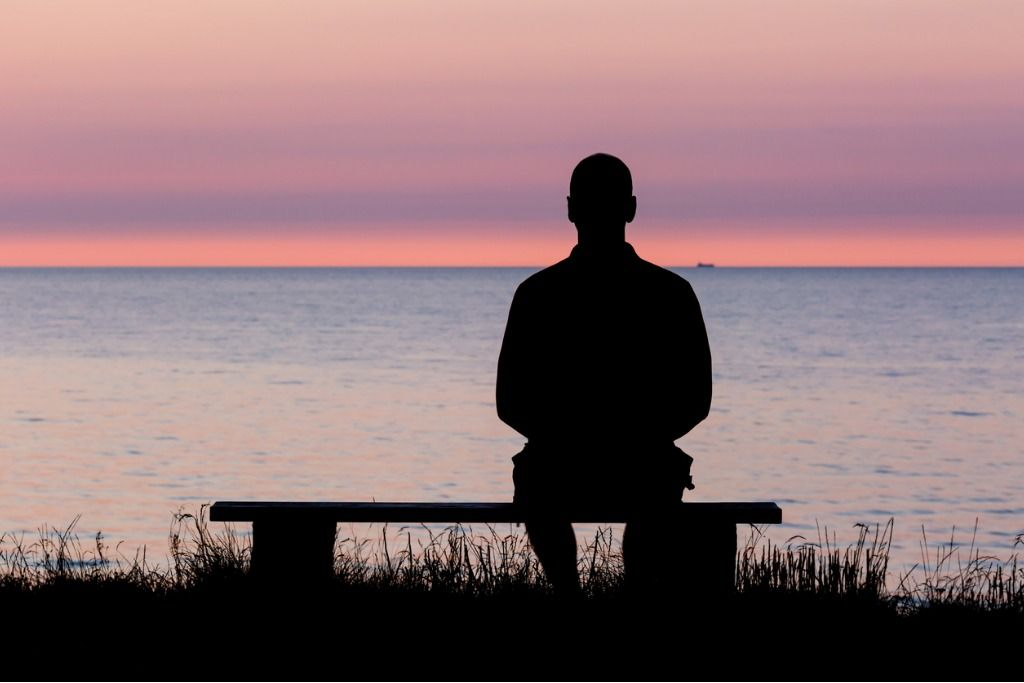 silhouette-of-man-on-bench-picture-id512131741