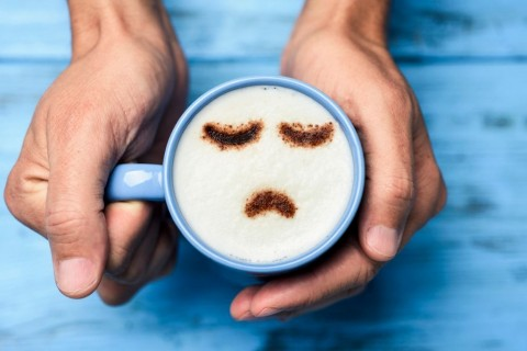 man-with-a-cup-of-cappuccino-with-a-sad-face-picture-id901912720