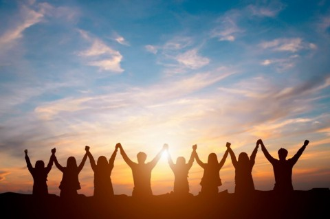 silhouette-of-happy-business-team-making-high-hands-in-sunset-sky-picture-id696209402