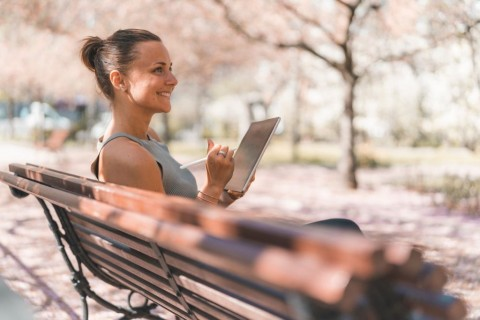 female-student-is-studying-in-a-cherry-blossom-park-picture-id987914458