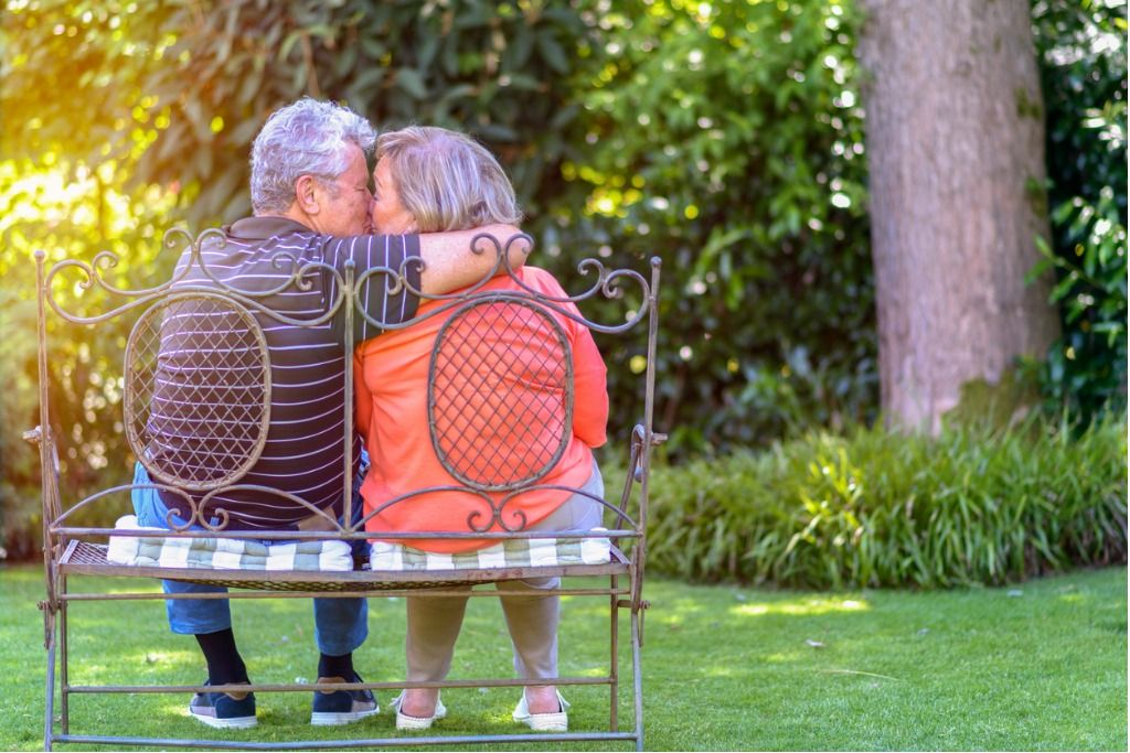 senior-kissing-on-bench-in-garden-picture-id824819810