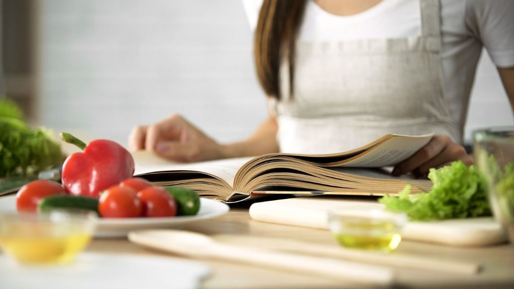 housewife-reading-cooking-book-with-fresh-vegetables-and-kitchen-on-picture-id923488706
