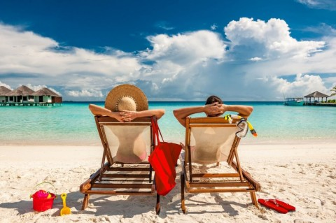 couple-in-loungers-on-beach-at-maldives-picture-id672425798