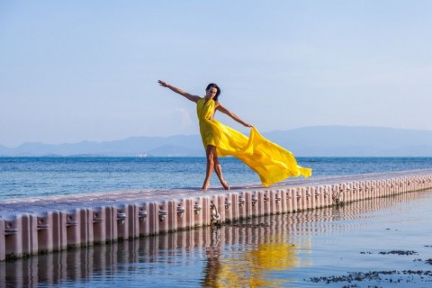 woman-in-flying-yellow-dress-on-pontoon-bridge-picture-id586159890