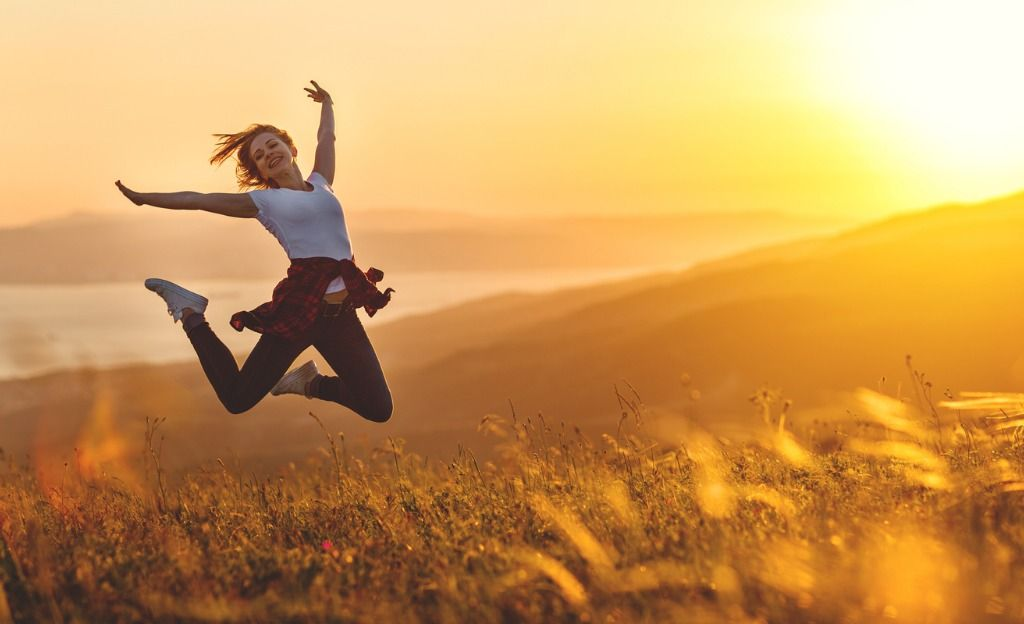 happy-woman-jumping-and-enjoying-life-at-sunset-in-mountains-picture-id931873664