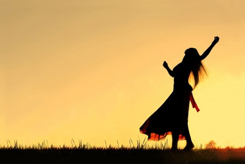 silhouette-of-woman-dancing-and-rejoicing-to-god-at-sunset-picture-id523033651