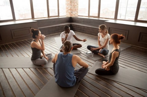 africanamerican-yoga-instructor-talking-to-diverse-group-sitting-on-picture-id922482728