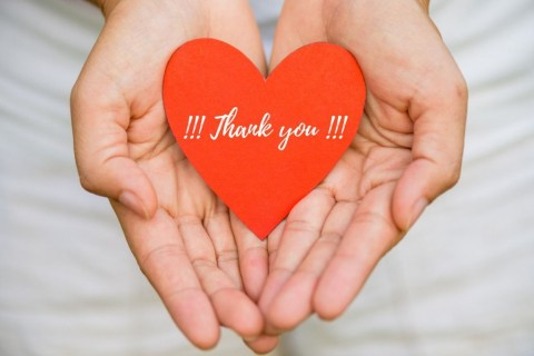young-woman-hand-holding-red-heart-paper-with-thank-you-message-picture-id926036786
