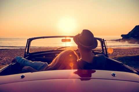 couple-watching-the-sunset-in-a-convertible-car-picture-id514059558