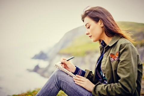 beautiful-young-woman-writing-in-diary-while-sitting-on-mountain-picture-id855120740