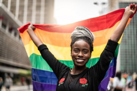 woman-waving-rainbow-flag-at-gay-parade-picture-id972902056