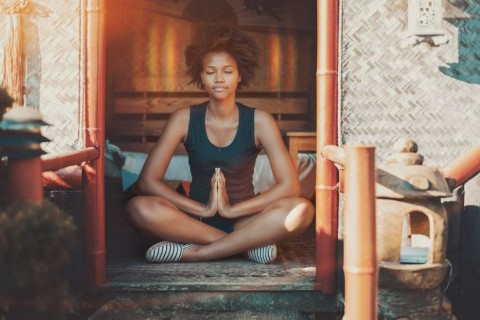 afro-girl-meditating-with-glow-over-her-head-picture-id874146814