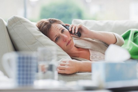 sick-woman-laying-on-sofa-talking-on-telephone-picture-id107429753