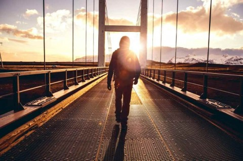 solo-traveler-walking-on-a-bridge-with-arm-raised-picture-id907634620