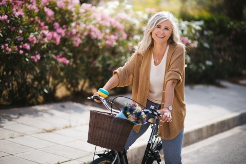 smiling-senior-woman-having-fun-riding-vintage-bike-in-spring-picture-id976787968
