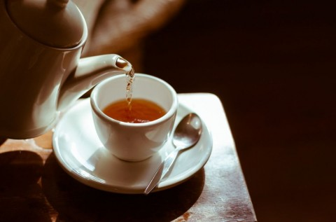 tea-cup-on-saucer-with-tea-being-poured-picture-id466073662