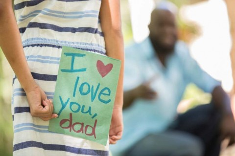 happy-fathers-day-girl-gives-card-to-dad-picture-id947482264
