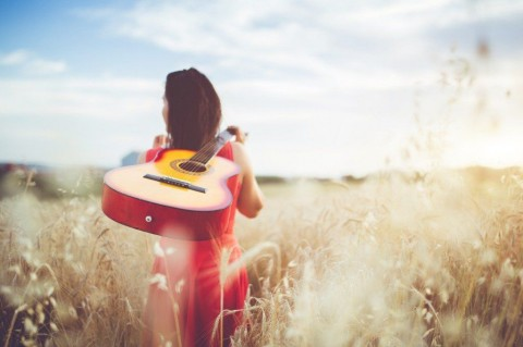 woman-walking-through-the-wheat-field-with-guitar-on-back-picture-id1146456569
