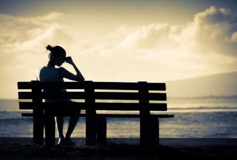 lonely-woman-sitting-alone-on-a-bench-picture-id957926688