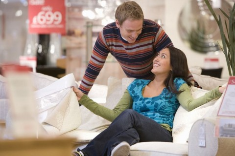 young-couple-shopping-man-smiling-at-woman-on-sofa-picture-id511554555