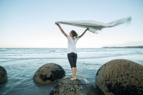 young-woman-stands-on-boulder-holds-blanket-in-the-air-picture-id521996604