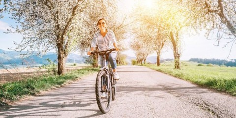 happy-smiling-woman-rides-a-bicycle-on-the-country-road-under-blossom-picture-id1131658795
