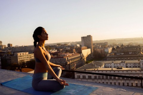 woman-in-lotus-position-meditating-on-the-rooftop-picture-id624671100