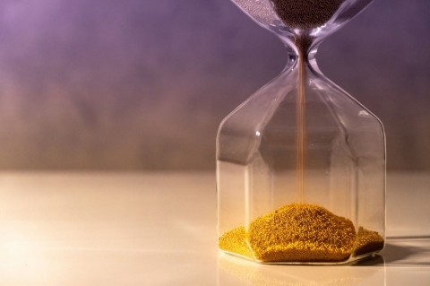 gold-sand-running-through-the-shape-of-modern-hourglass-on-white-picture-id1019220020