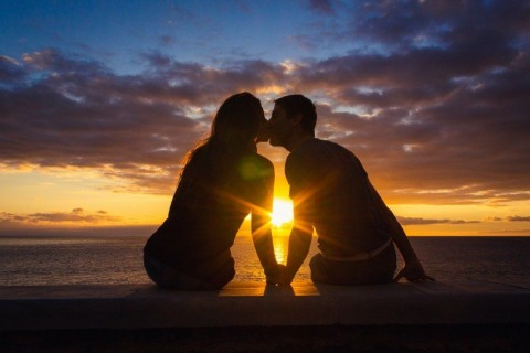 man-and-woman-sitting-by-the-sea-kissing-at-sunset-at-meloneras-beach-picture-id1124728680