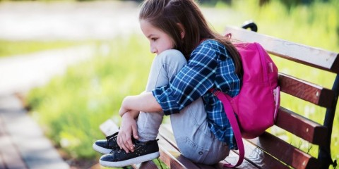 unhappy-schoolgirl-sitting-in-the-park-education-lifestyle-concept-picture-id1008019504