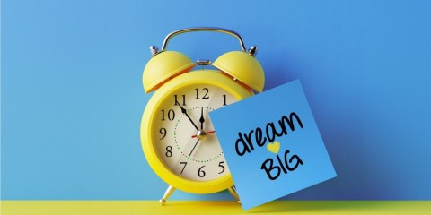 alarm-clock-and-a-blue-post-it-not-over-blue-background-picture-id905325758