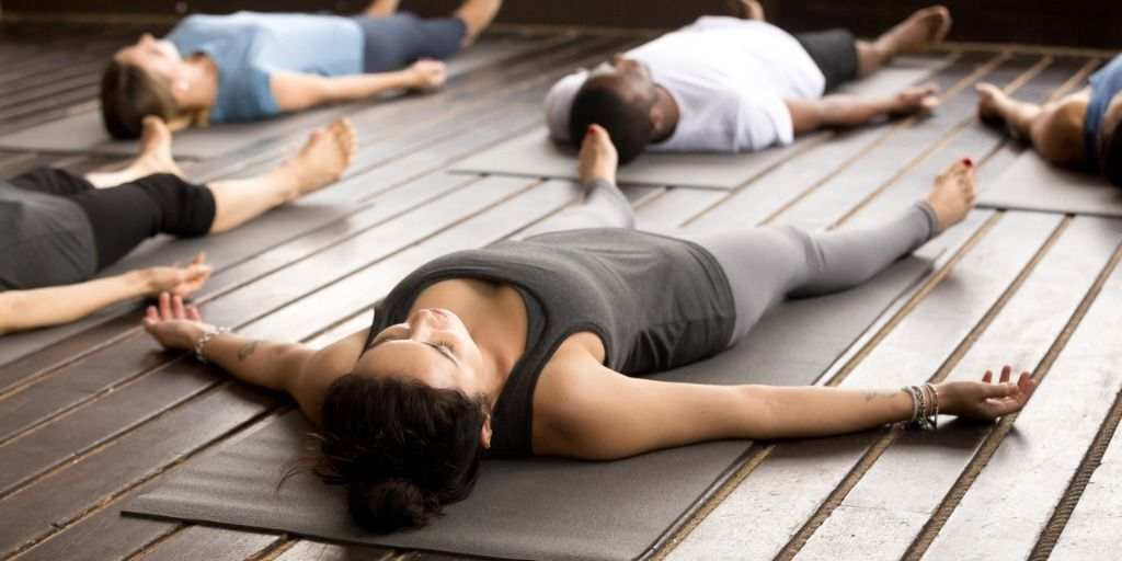 group-of-sporty-people-in-savasana-pose-picture-id922345076