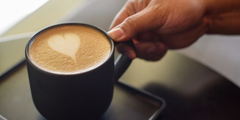 man-hand-taking-up-a-cup-of-coffee-with-heart-shape-froth-art-picture-id1158631503
