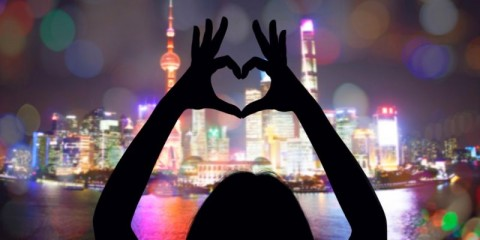 woman-making-a-heart-symbol-with-her-hands-towards-shanghais-pudong-picture-id1160646308-1
