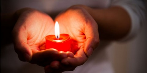 woman-hands-holding-burning-heartshaped-candle-picture-id1156845105