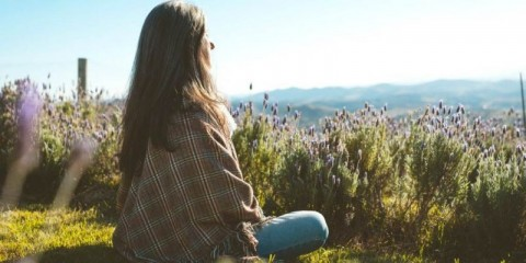 woman-meditating-in-the-nature-in-a-flower-field-with-closed-eyes-picture-id1161250308