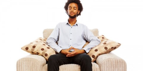 content-young-man-sitting-meditating-in-comfy-chair-on-white-picture-id106573189