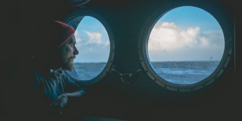 man-at-the-porthole-window-of-a-vessel-in-a-rough-sea-picture-id886706822