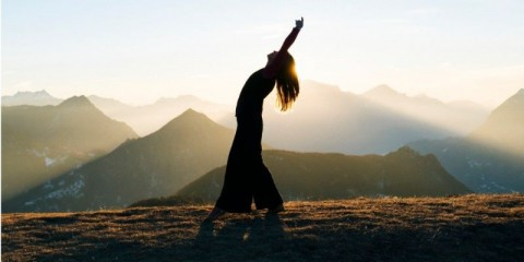 woman-dances-at-sunrise-in-the-mountains-picture-id942893092