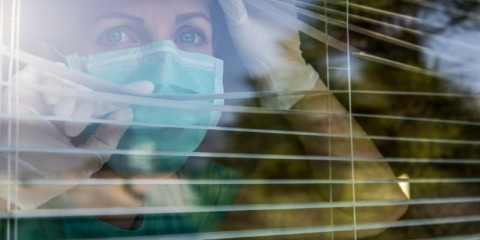 concerned-healthcare-worker-looking-through-a-window-picture-id1215311167