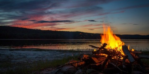 summer-campfire-and-lake-at-sunset-picture-id498849219