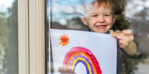 young-boy-sticking-his-drawing-on-home-window-during-the-covid19-picture-id1214595977