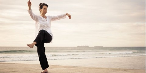 woman-standing-poised-practicing-wu-tai-chi-on-the-end-of-a-concrete-picture-id934788776