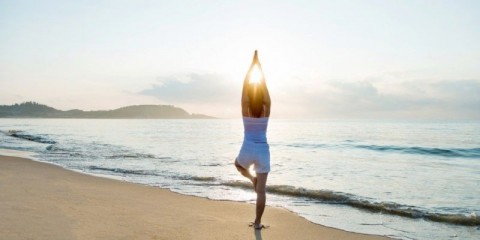 woman-doing-yoga-at-the-beach-picture-id1177568976