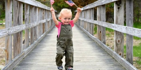 young-boy-carrying-american-flag-over-bridge-picture-id1151203312