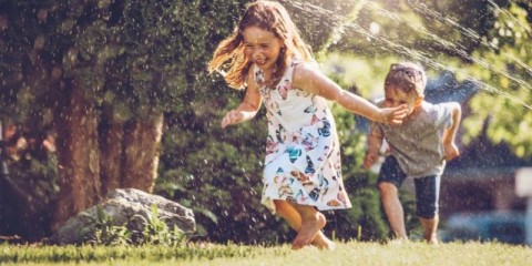 happy-kids-playing-with-garden-sprinkler-picture-id1159180335