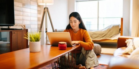 young-woman-using-laptop-comfortably-at-home-picture-id1202760401